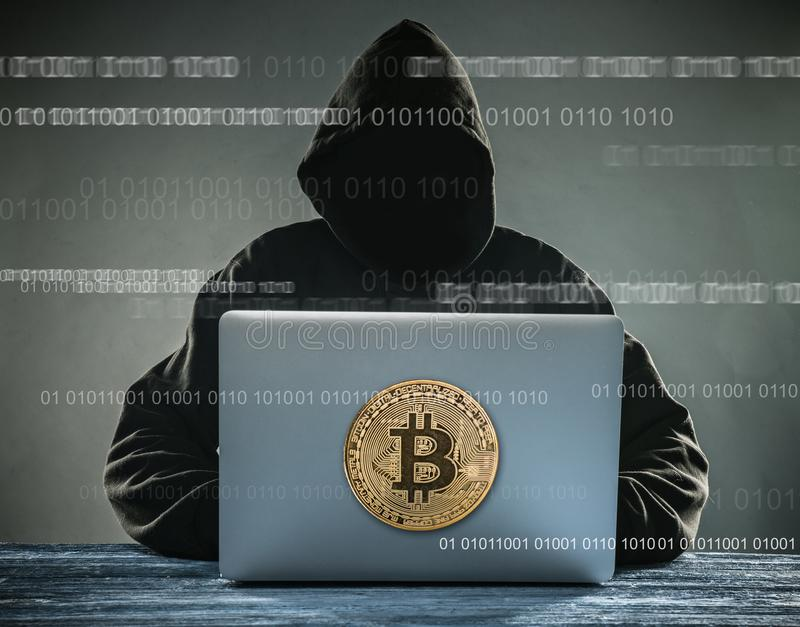 Moeda de ouro de Bitcoin e sittign anônimo do hacker com portátil imagem de stock royalty free
