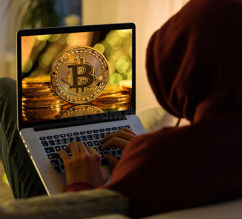 Moeda de ouro de Bitcoin e sittign anônimo do hacker com portátil imagens de stock