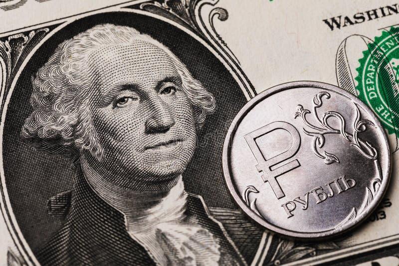 1 moeda de ouro contra o fundo da nota de 1 dólar Na moeda está inscrita a inscrição em letras russas ruble imagens de stock