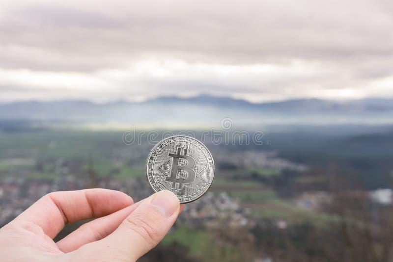 Moeda de prata de Bitcoin, bitcoin da posse da mão acima da cidade imagem de stock