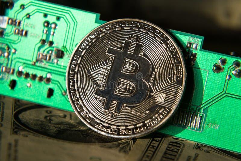 Moeda de prata do bitcoin com dólares e cartão-matriz do computador, mineração do cryptocurrency e investimento foto de stock royalty free