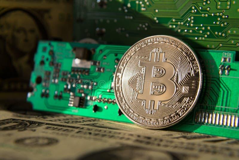 Moeda de prata do bitcoin com dólares e cartão-matriz do computador, mineração do cryptocurrency e investimento fotografia de stock royalty free