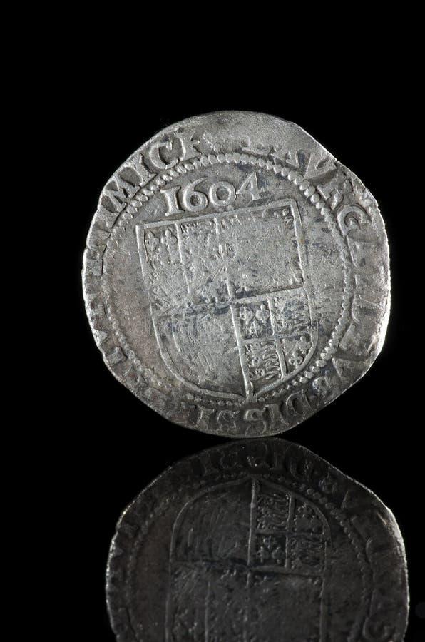 Moeda de prata velha, martelada exposta no vidro refletindo preto, fou foto de stock royalty free