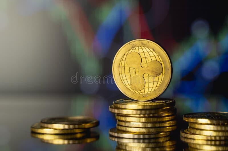 Moeda de réplica e conceito de moeda virtual Ripple do Ouro numa pilha de moedas com um gráfico de crescimento e valorização decr foto de stock