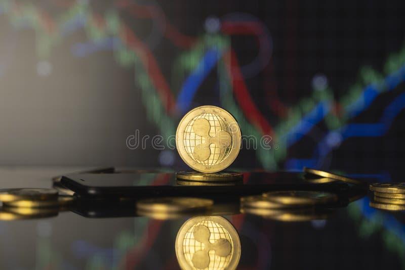 Moeda de réplica e conceito de moeda virtual Ripple do Ouro numa pilha de moedas com um gráfico de crescimento e valorização decr fotos de stock