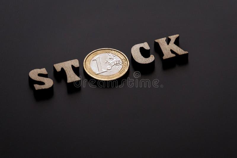 Moeda de um euro entre as letras de madeira que compõem a palavra ESTOQUE Fundo preto da textura Profundidade de campo rasa Close imagem de stock royalty free