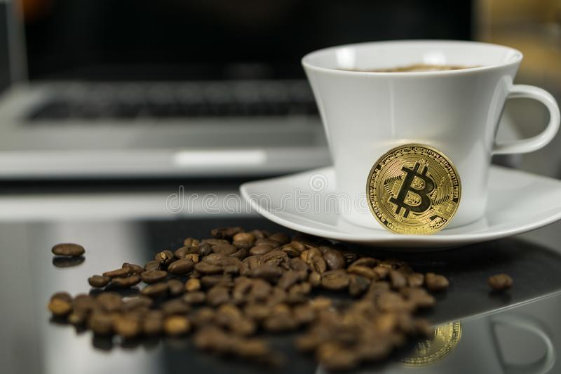 Moeda do cryptocurrency de Bitcoin com copo de café e feijões de café imagem de stock royalty free