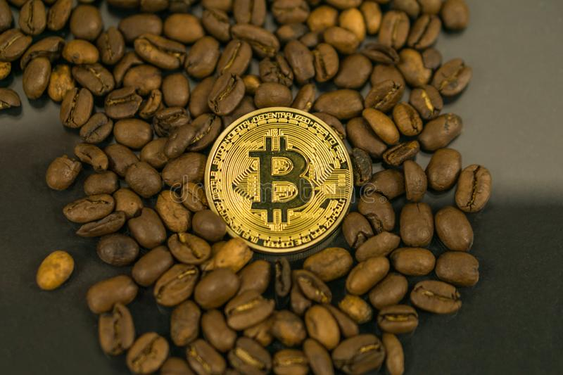 Moeda do cryptocurrency de Bitcoin como a moeda do pagamento cercada com feijões de café fotografia de stock royalty free