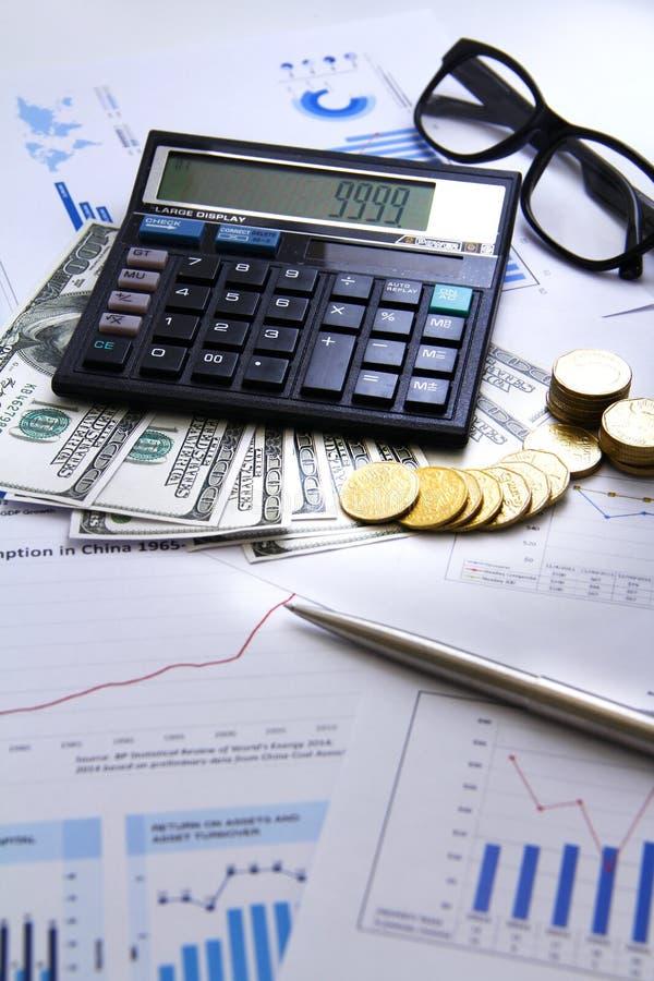 A moeda do dinheiro da contagem do homem de negócios com gráficos de negócio da calculadora e as cartas relatam na tabela imagem de stock