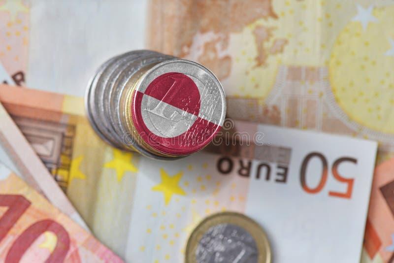 Moeda do Euro com a bandeira nacional de greenland no euro- fundo das cédulas do dinheiro foto de stock royalty free