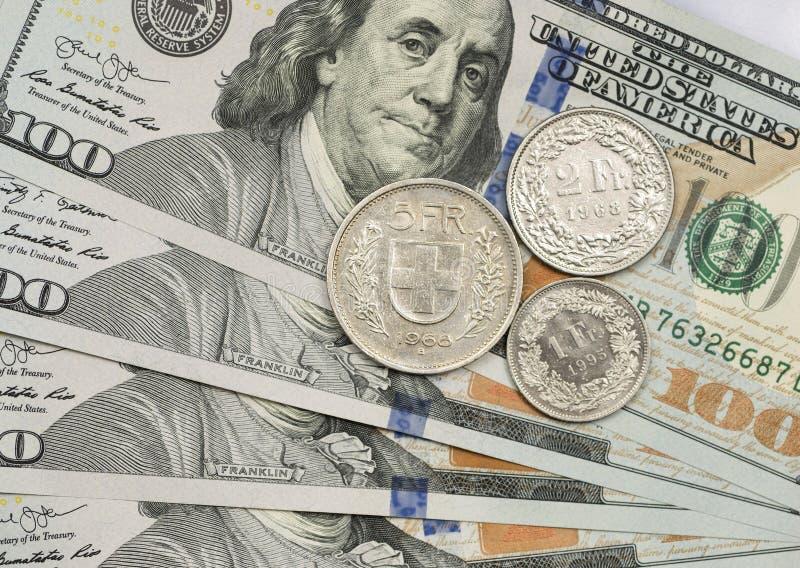 Moeda do franco suíço sobre notas de dólar fotografia de stock royalty free