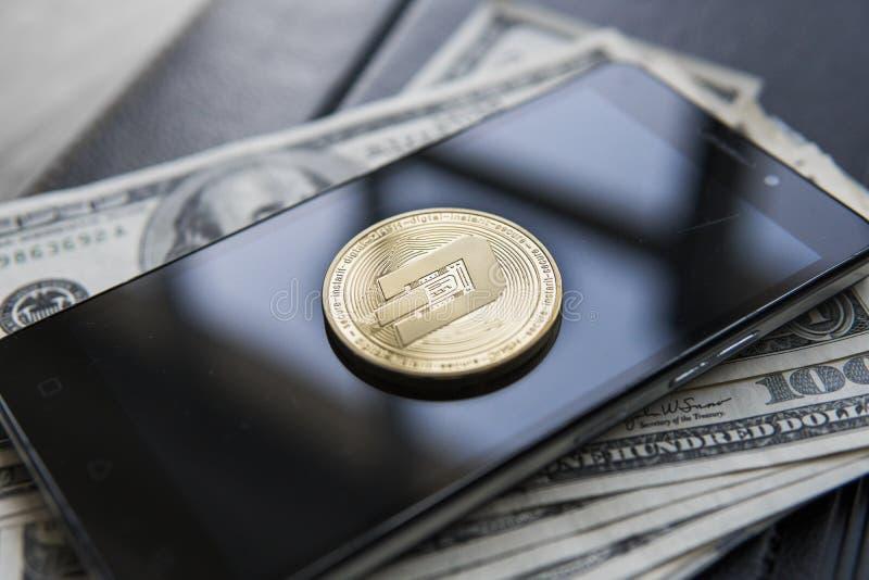 Moeda dourada de Cryptocurrency do traço em uma pilha de dólares americanos e de caderno do smartphone Dinheiro do dinheiro e con fotos de stock royalty free