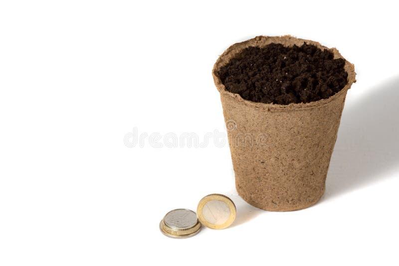 Moeda e um potenciômetro da turfa para as plântulas que encontram-se junto, em uma empresa rural da produção agrícola isolada sob foto de stock