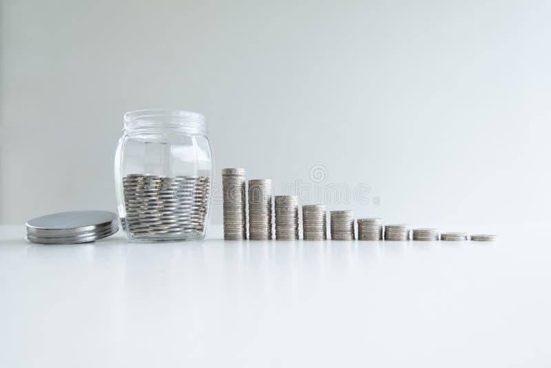 Moeda no banco da garrafa de vidro com gráfico de barra das moedas imagem de stock royalty free