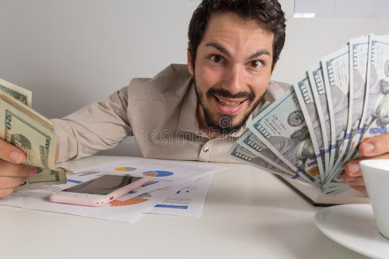 Moeda norte-americana: Dólar Adulto novo que guarda muitas contas na tabela imagem de stock