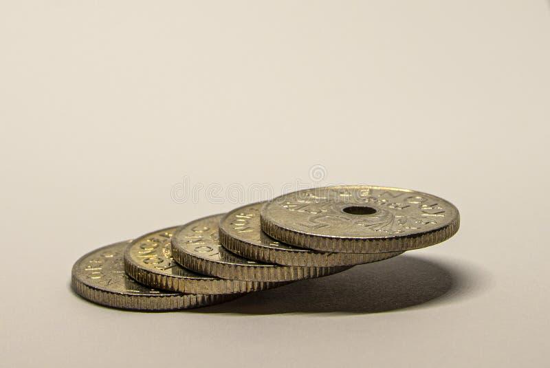 Moedas coloridas de prata empilhadas em uma tabela imagem de stock royalty free