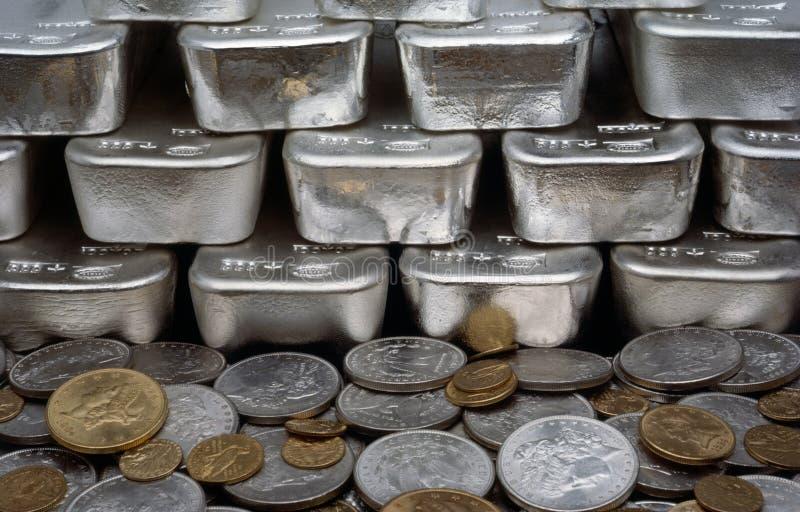 Moedas da prata e de ouro com barras de prata fotografia de stock royalty free