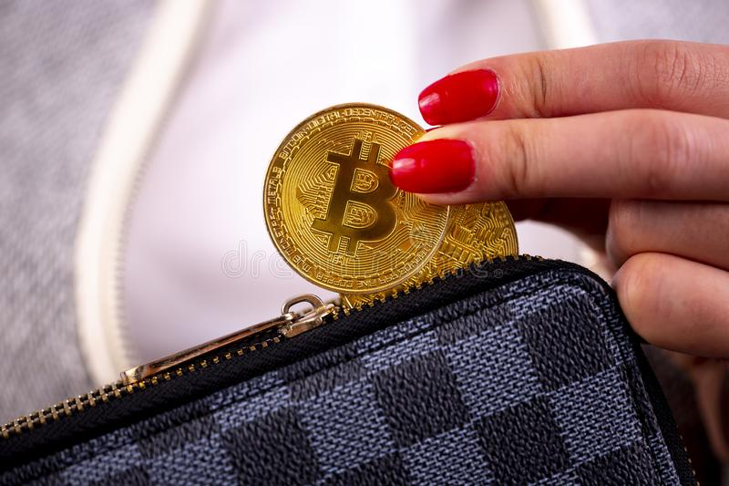 Moedas de Bitcoin na bolsa da mão da mulher fotos de stock