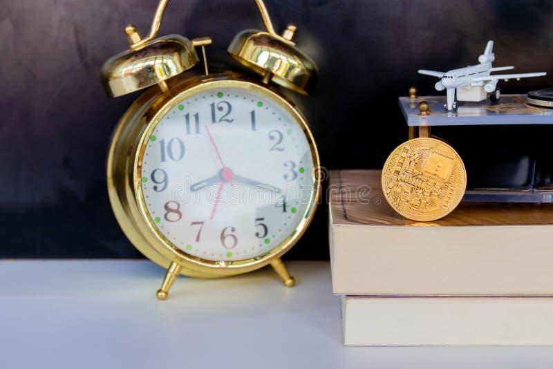 Moedas de Bitcoin no ouro velho do despertador do livro e no modelo do avião comercial sobre o fundo preto branco fotos de stock royalty free