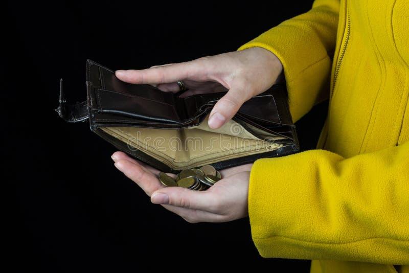 Moedas de derramamento da menina fora de uma bolsa, fundo preto, close-up, moeda foto de stock