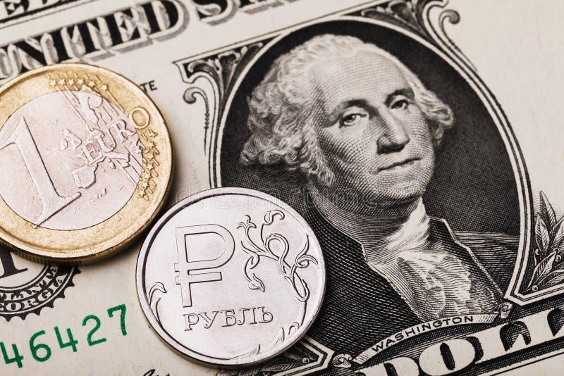 Moedas de 1 euro e 1 rublo russo contra o fundo de uma nota de dólar Na moeda está inscrita a inscrição em letras russas ruble imagem de stock royalty free