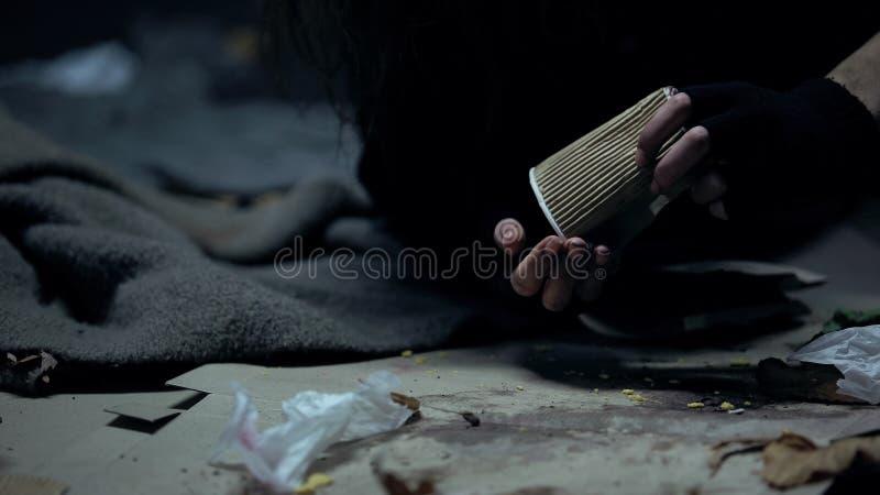 Moedas de jogo da mulher desabrigada do copo de papel, contando doações, caridade foto de stock