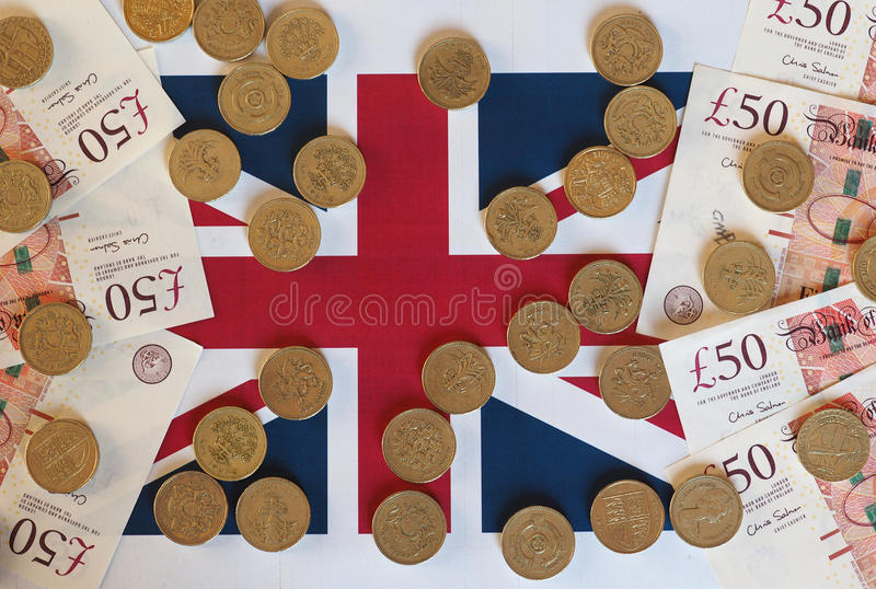 Moedas de libra e notas, Reino Unido sobre a bandeira imagem de stock royalty free