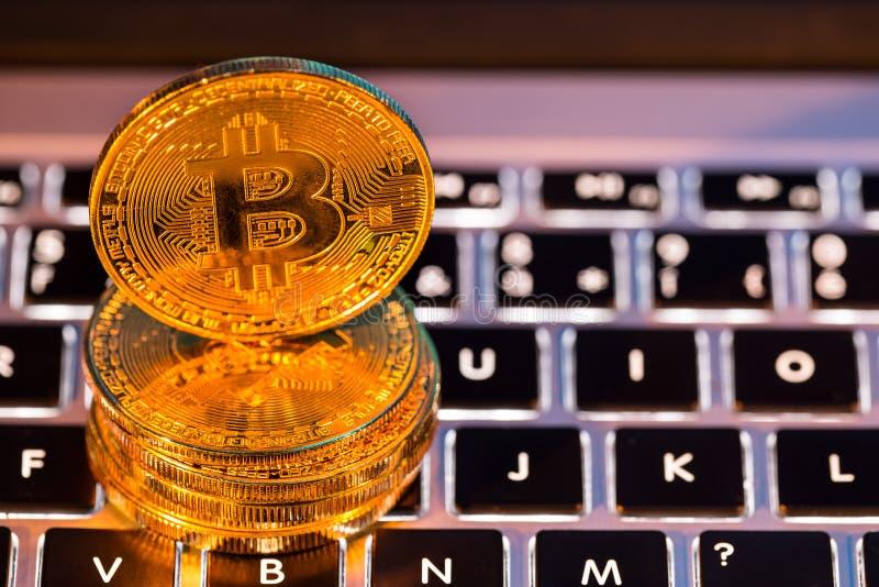 Moedas de ouro de Bitcoin com teclado do portátil Conceito virtual do cryptocurrency imagem de stock