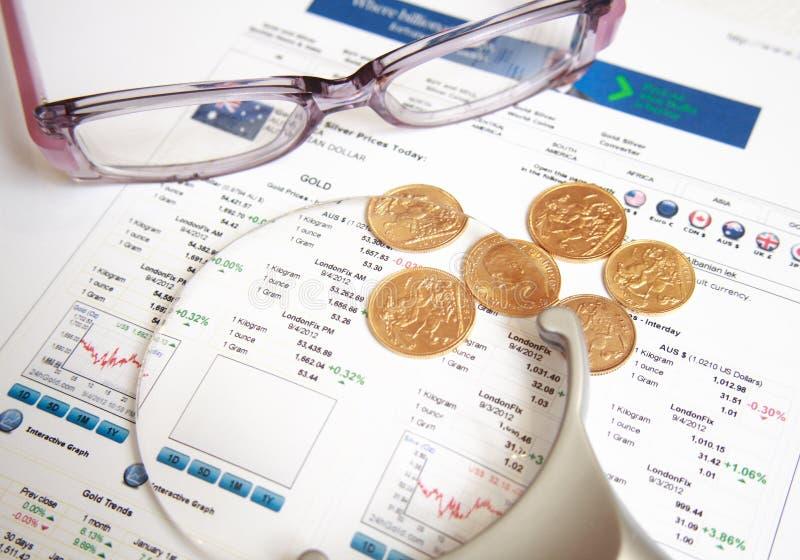 Moedas de ouro com eyeglasses e magnifier imagens de stock royalty free