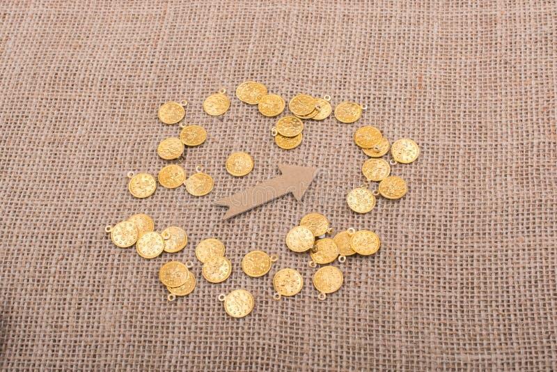 Download Moedas De Ouro Falsificadas Em Torno Da Forma Da Seta Foto de Stock - Imagem de financeiro, conceptual: 107525486