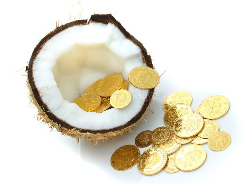 Moedas de ouro mantidas dentro de um coco fotografia de stock
