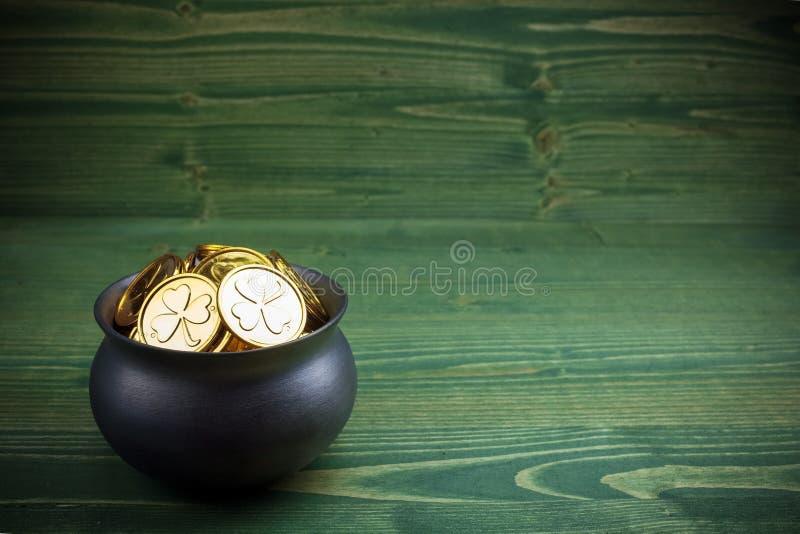 Moedas de ouro na caldeira para o dia dos patricks do st no fundo de madeira verde foto de stock royalty free