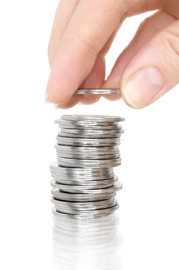 Moedas de prata da pilha com reflexão e mão fotos de stock royalty free