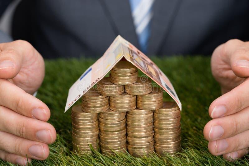 Moedas de Protecting House Of do homem de negócios e nota do Euro na grama fotos de stock royalty free
