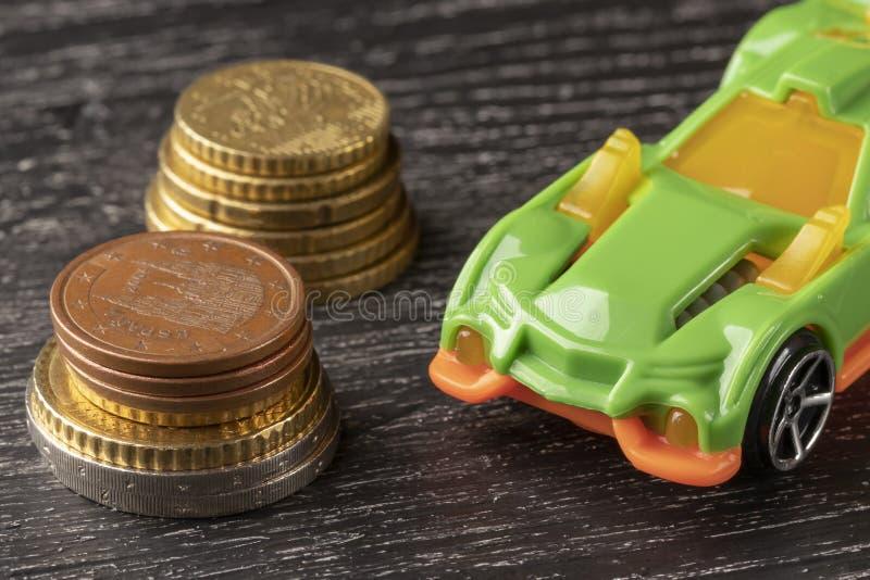 Moedas do brinquedo e do euro do carro em um fundo de madeira escuro foto de stock