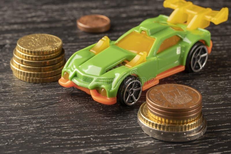 Moedas do brinquedo e do euro do carro em um fundo de madeira escuro fotos de stock royalty free