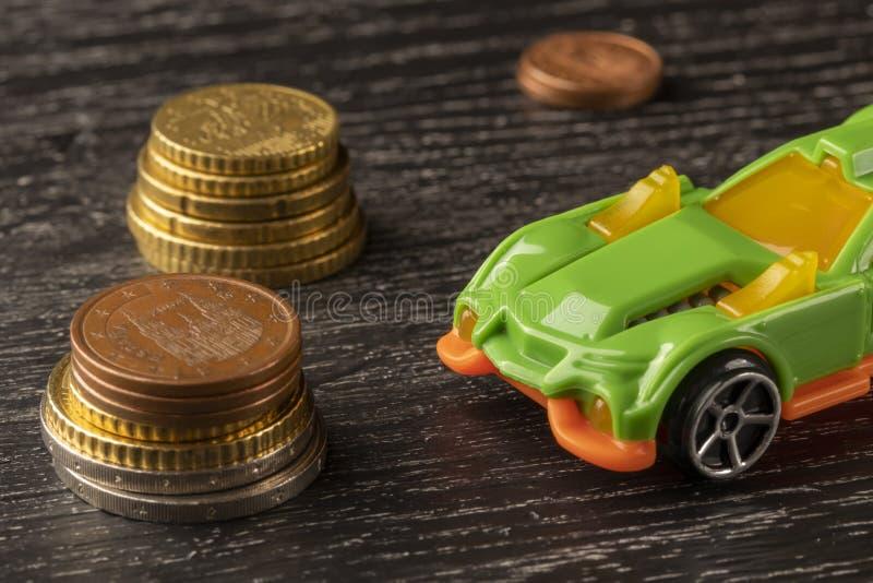 Moedas do brinquedo e do euro do carro em um fundo de madeira escuro fotografia de stock