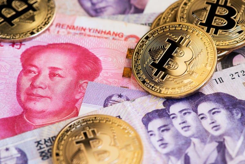 Moedas do cryptocurrency de Bitcoin na moeda de China Yuan Renminbi e nas cédulas ganhadas norte-coreanas próximas acima da image foto de stock royalty free