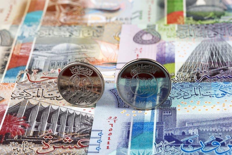 Moedas do dinar kuwaitiano no fundo das cédulas fotografia de stock royalty free
