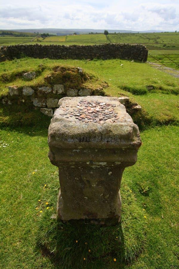 Moedas do dinheiro velho na coluna de pedra imagem de stock
