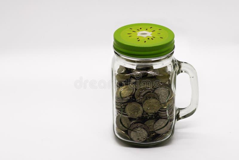 Moedas do metal no frasco de vidro do frasco de pedreiro no fundo branco fotografia de stock royalty free