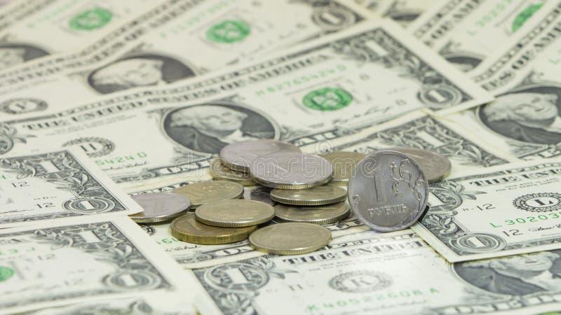 Moedas do rublo de russo contra um fundo das cédulas do dólar dos EUA fotos de stock