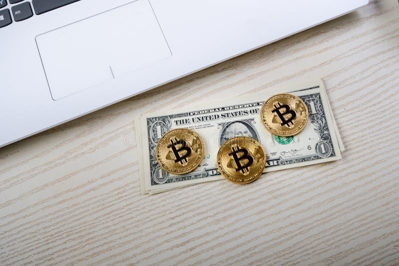 Moedas douradas de Bitcoin em uma tabela com cédulas e portátil do dólar Dinheiro virtual Negócio de Cryptocurrency Fundo do escr fotografia de stock