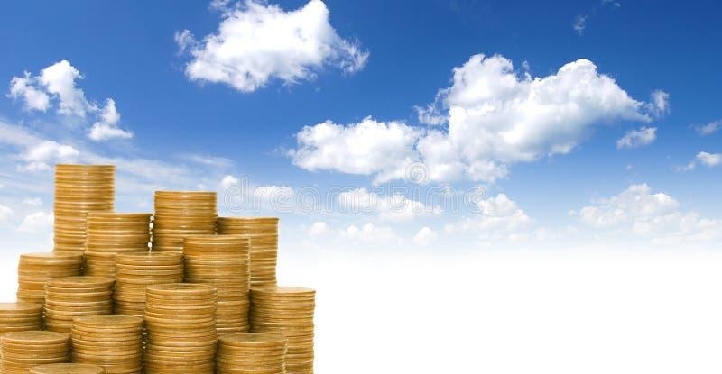 Moedas douradas de encontro ao céu azul foto de stock royalty free
