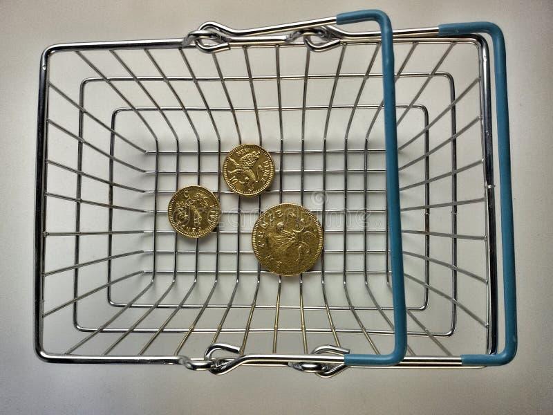 Moedas douradas dentro da cesta metálica fotografia de stock