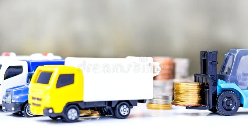 Moedas douradas empilhadas no caminhão de empilhadeira no fundo cinzento imagem de stock