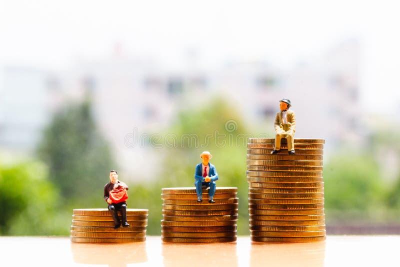 Moedas e pessoas adultas no fundo da natureza; economia do dinheiro fotografia de stock