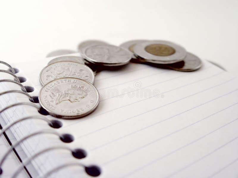 Moedas em um caderno espiral imagens de stock royalty free