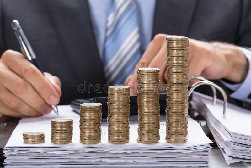 Moedas empilhadas Calculating Invoice With do homem de negócios imagens de stock royalty free
