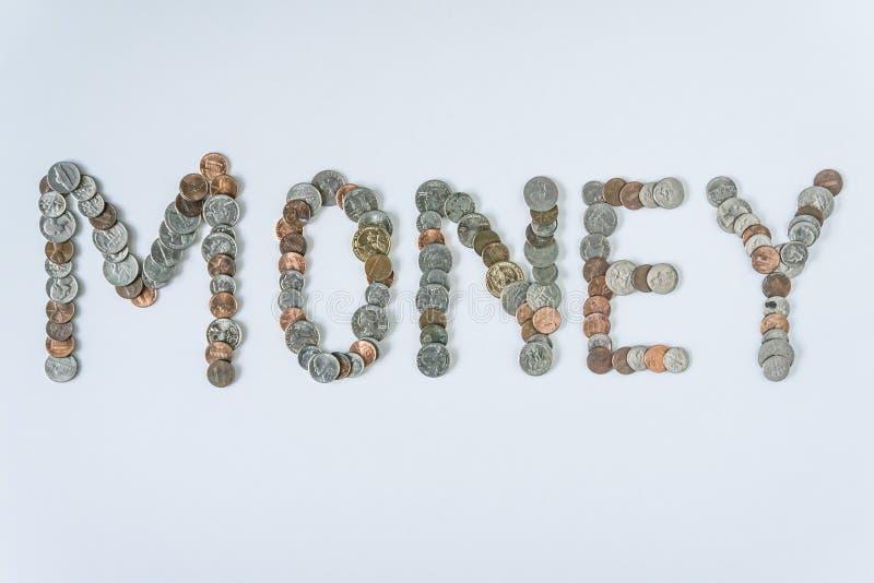 Moedas isoladas no fundo branco contínuo que soletra o dinheiro da palavra imagem de stock royalty free